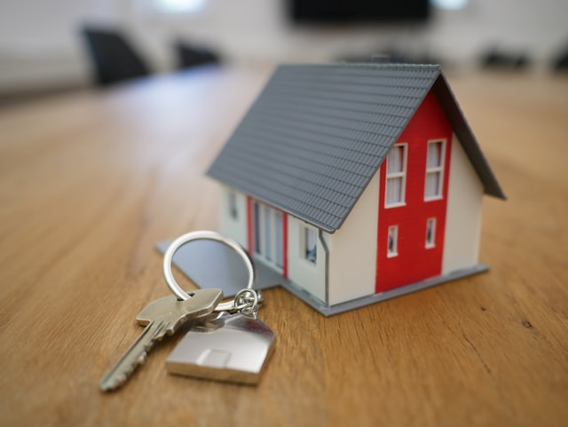 Model of a house next to a real-sized key and keyring